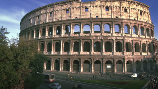slow motion, angled pan shot of colosseum to street - arch of constantine stock videos and b-roll footage