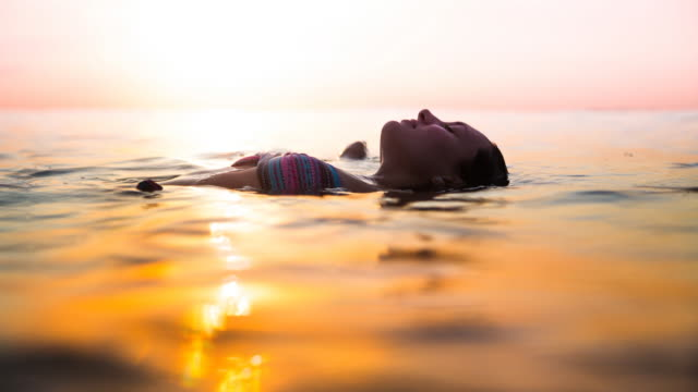 slow motion animation of a traveler woman floating on water resting during sunset moment after long day during travel vacations in the paradise islands of indonesia with stunning colors in the sky and reflections on water in movement. - flyta på vatten bildbanksvideor och videomaterial från bakom kulisserna
