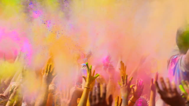 Slow motion animation of colorful Holi party with people throwing dust of colors to the air with arms raised during the most excitement moment in the celebration.