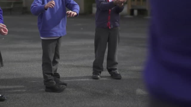 slow motion anonymous shots of schoolchildren playing in school playground - foot stock videos & royalty-free footage