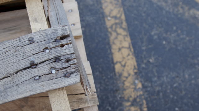 slow motion artistic close-up shot of man-made wooden pine pallets on an outdoor warehouse loading dock for bulk heavy freight shipping or diy home made art projects - wood grain stock videos & royalty-free footage