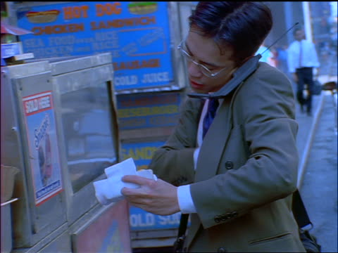 BLUE slow motion Asian businessman talking on cellular phone buys hot dog from vendor on NYC sidewalk