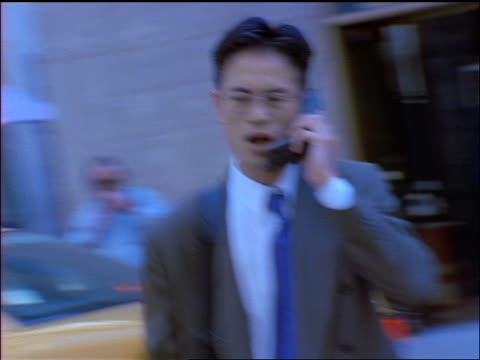 blue slow motion asian businessman talking on cellular phone + walking on nyc street - yuppie stock videos and b-roll footage
