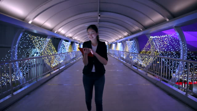 4k slow motion : asian businesswoman walking at the skywalk and she played the tablet during the night - elevated walkway stock videos & royalty-free footage