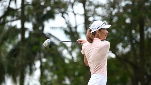 slow motion asian chinese female golfer playing golf teeing off - golf club stock videos & royalty-free footage
