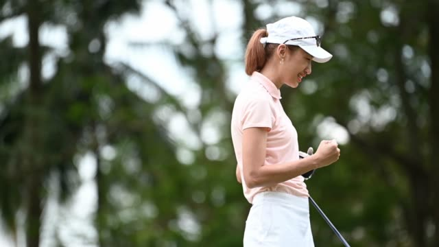 slow motion asian chinese female golfer playing golf teeing off - golf stock videos & royalty-free footage