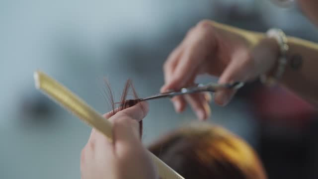 slow motion asian chinese hairstylist female cutting hair for her customer in hair saloon - brown hair stock videos & royalty-free footage