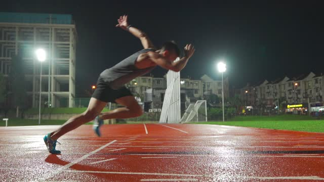 slow motion asian chinese male athlete running at men's track rainy late evening in stadium - sportsperson stock videos & royalty-free footage