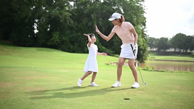 slow motion asian chinese parent golfer teaching daughter playing golf at golf course weekend - sporting term stock videos & royalty-free footage