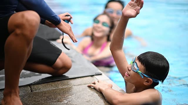 slow motion asian chinese swim coaches showing record stopwatch to a teenage boy after the family swimming across s - swimming goggles stock videos & royalty-free footage