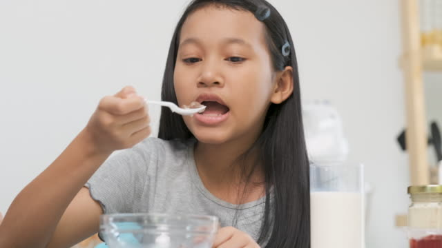 slow motion asian daughter eating breakfast cereal in morning at home kitchen - spoon stock videos & royalty-free footage