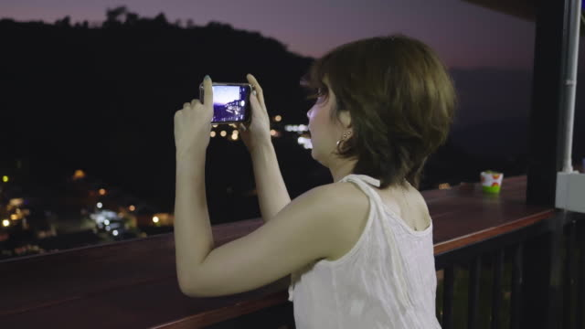 slow motion asian girl take a photo in holiday at night - photographer stock videos & royalty-free footage