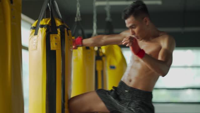 vidéos et rushes de au ralenti malais asiatique muay thai boxer volant kick punching sacs dans le club de santé gym - endurance