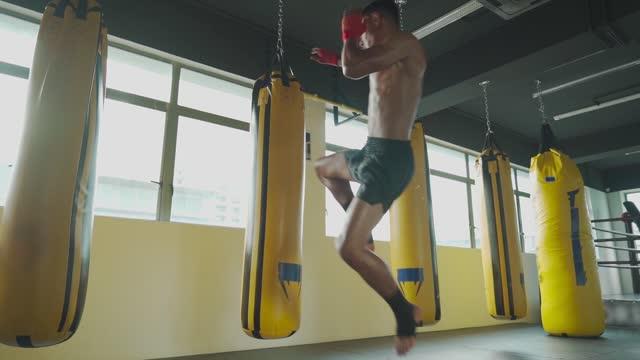 zeitlupe asiatische malay muay thai boxer fliegen kick boxsäcke in gym health club - menschliches knie stock-videos und b-roll-filmmaterial