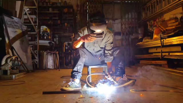 slow motion asian malay welder welding working in the workshop with welding torch repairing - foreman stock videos & royalty-free footage