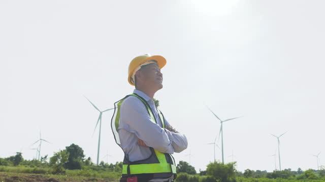 vidéos et rushes de ralenti ingénieur asiatique masculin marchant et regardant l'éolienne énergie éolienne énergie éolienne renouvelable nature énergie éolienne fond. homme ingénieur portant un casque et un gilet réfléchissant - bras croisés