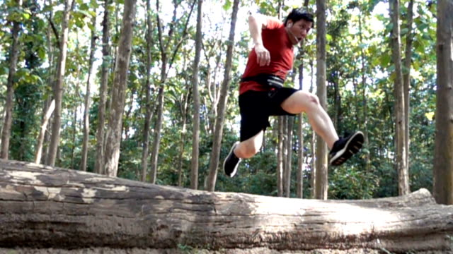 Slow motion Asian man jumping across log wood in trail running in forest