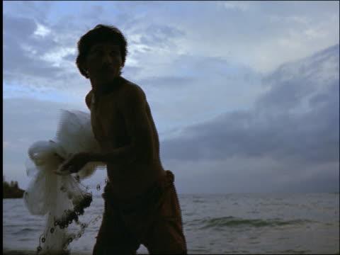 slow motion asian man throwing fishing net into ocean / ulu watu / bali / indonesia - one mid adult man only stock videos & royalty-free footage