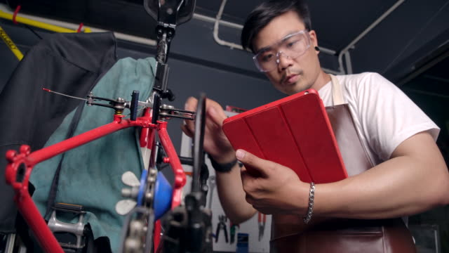 4k slow motion asian men wear glasses he is the owner of a bicycle shop. is a small business he is fixing the bike and spinning the wheel. he is using a tablet to check the product, see the professional. - repairing stock videos & royalty-free footage