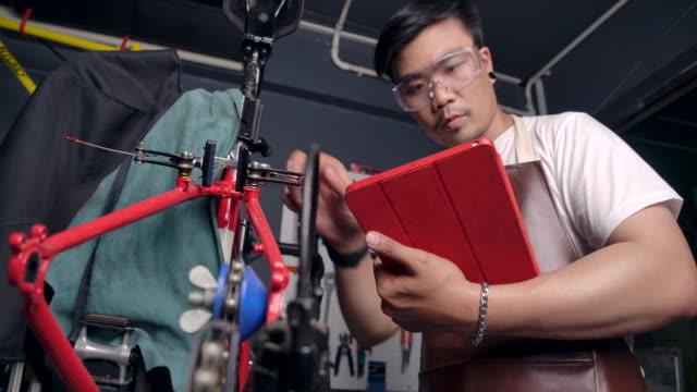 stockvideo's en b-roll-footage met 4k slow motion aziatische mannen dragen glazen hij is de eigenaar van een fietsenwinkel. is een klein bedrijf dat hij is het repareren van de fiets en het draaien van het wiel. hij gebruikt een tablet om het product te controleren, zie de professional. - herstel