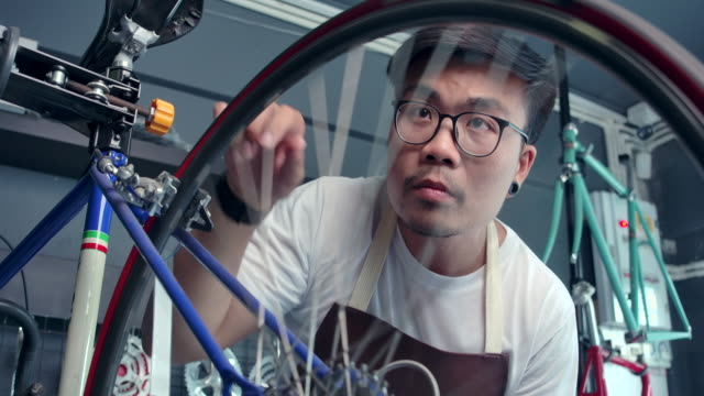 4k slow motion asian men wear glasses he is the owner of a bicycle shop. is a small business he is fixing the bike and spinning the wheel. he is using a tablet to check the product, see the professional. - spinning stock videos & royalty-free footage