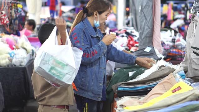 slow motion : asiatiska mor och barn handla kläder på marknaden bås - editorial bildbanksvideor och videomaterial från bakom kulisserna
