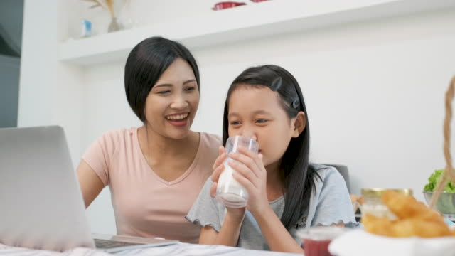 slow motion asian mother and daughter watching video on laptop together in kitchen with smile face and drinking milk.learning at home. - offspring stock videos & royalty-free footage