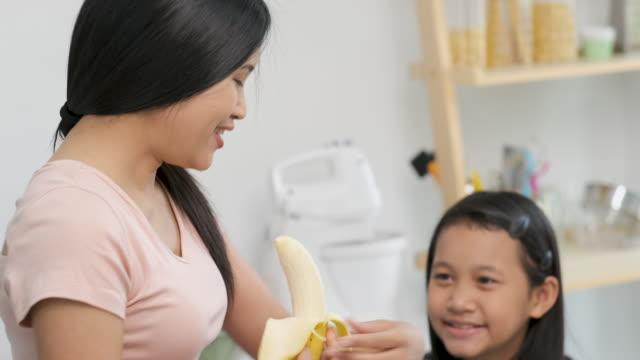 vídeos y material grabado en eventos de stock de lento movimiento asiático madre alimentando plátano a hija en la cocina en casa - potasio