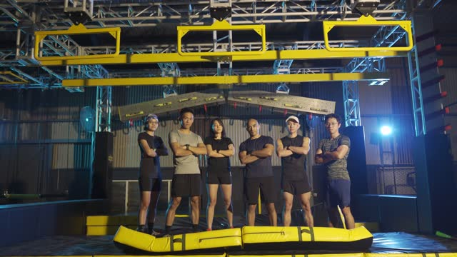 slow motion asian multi ethic group of sport team arms crossed looking at camera with cool attitude with winning completing indoor obstacle course challenge - attitude stock videos & royalty-free footage