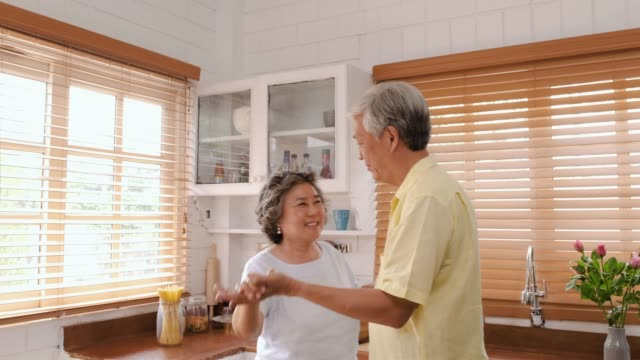 slow motion asian seniors couple enjoy dancing in kitchen at home.aging at home concept - slow dancing stock videos and b-roll footage