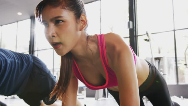 4k uhd slow motion : asian sporty woman and team in sportswear is doing mountain climber exercise on the floor at indoor gym. - endurance stock videos & royalty-free footage