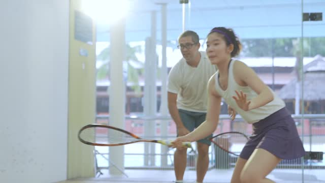 slow motion asian squash coach guiding teaching his  student squash showing them in the game - racquet stock videos & royalty-free footage