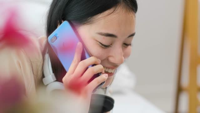 自宅でベッドルームでモバイルとヘッドフォンでベッドの上にラップトップを使用しているときに携帯電話で話すスローモーションアジアの十代の女性。感情をリラックス家で働くぼかしの� - 電話を使う点の映像素材/bロール