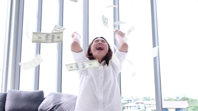 お金を保持しているモーション アジア女性をゆっくりし、自宅で空気で投げる - 宝くじ点の映像素材/bロール