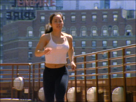 slow motion asian woman running on roof of building toward camera / buildings in background / nyc - spandex stock videos & royalty-free footage