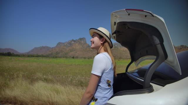 vídeos y material grabado en eventos de stock de 4k mujer asiática a cámara lenta viajó en coche privado. y estacionado en varios lugares ella está feliz de viajar - maletero