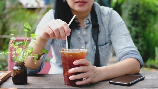 日当たりの良い day.summer の飲み物にコーヒー ショップでアイスティーを攪拌スローモーション アジア女性 - アイスティー点の映像素材/bロール