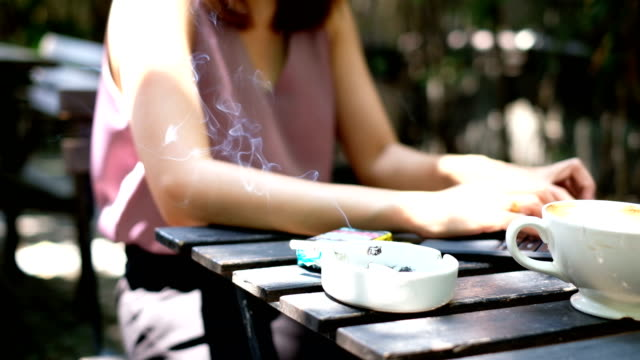 4k slow motion : asian woman taking break from her work to smoking cigarette in coffee cafe. - no smoking sign stock videos & royalty-free footage