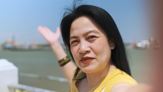 slow motion asiatisk kvinna vlog på staden nära floden i soliga dagen när du reser - följa rörlig aktivitet bildbanksvideor och videomaterial från bakom kulisserna