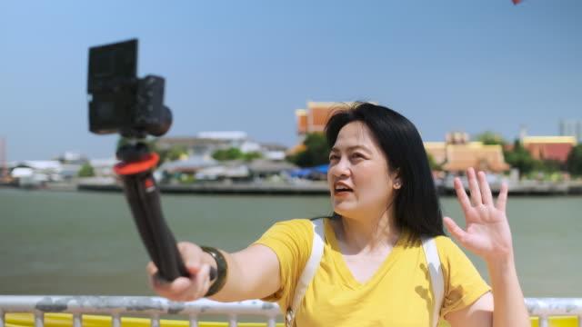 slow motion asiatisk kvinna vlog på city nära floden i soliga dagar när du reser - följa rörlig aktivitet bildbanksvideor och videomaterial från bakom kulisserna