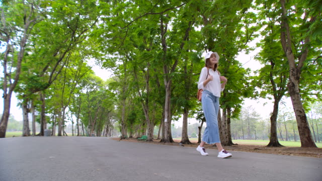4k slow motion asian woman walking in the park - ethereal stock videos & royalty-free footage