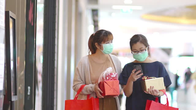 slow motion asian women shopping with face mask on for protection - paper bag stock videos & royalty-free footage