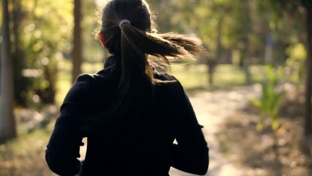vídeos de stock e filmes b-roll de slow motion , asian young athlete woman running in park - membro