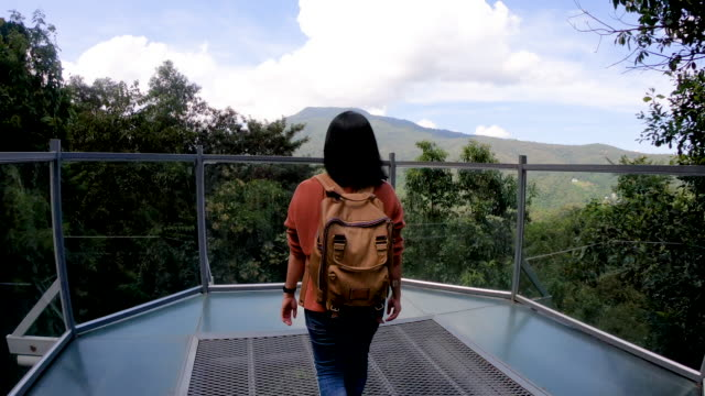 slow motion asianwoman backpack walking on canopy trail and reach view point at mountain view