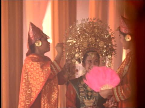 slow motion attendants fan + apply headdress to mingangkaubau bride / bukittingi, west sumatra - headdress stock videos & royalty-free footage