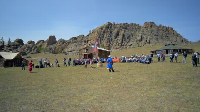 slow motion: audience around wrestlers fighting on field during naadam against sky - ulaanbaatar, mongolia - film festival stock videos & royalty-free footage