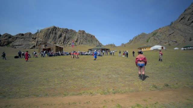 slow motion: audience watching wrestlers fighting on field during naadam - ulaanbaatar, mongolia - film festival stock videos & royalty-free footage