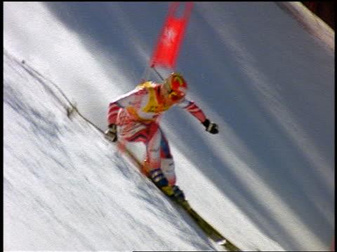 slow motion PAN Austrian downhill skier skiing down steep slope past flag / Colorado