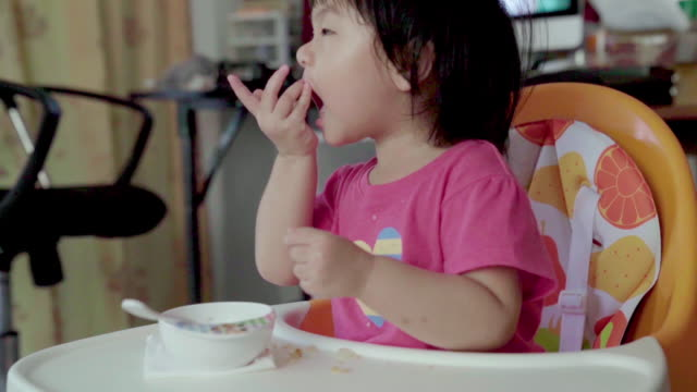 slow motion baby girl eating fried rice on table - root vegetable stock videos and b-roll footage
