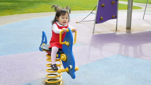 slow motion baby girl play rocking horse